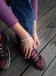 Knyter skorna med ett armband med texten Siblings på.